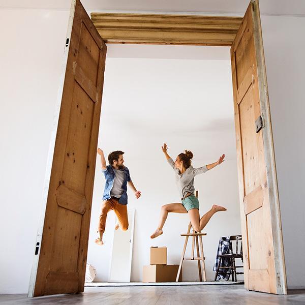 dwie osoby skaczące widziane przez drzwi